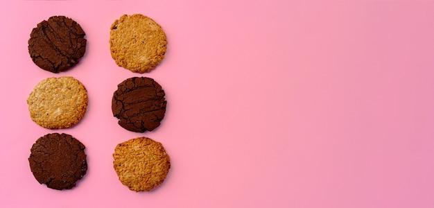Biscuits au chocolat et biscuits à l'avoine sur fond rose, bannière avec espace copie, vue du dessus