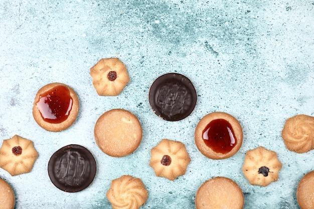 Biscuits au chocolat et confiture sur fond bleu.