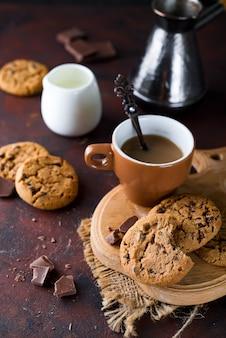 Biscuits au chocolat dans une assiette et une tasse de café chaud