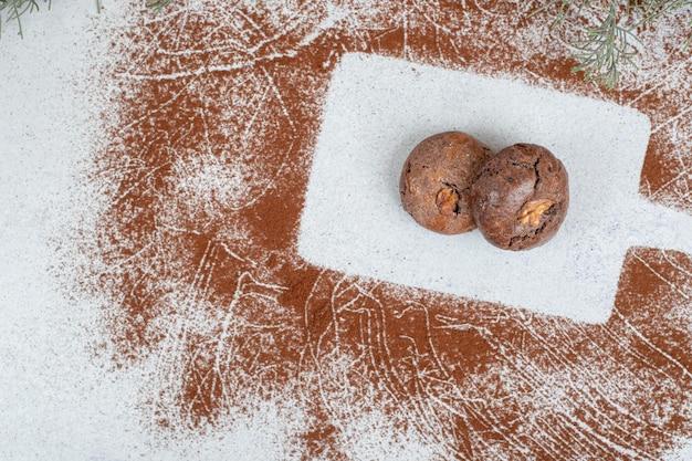 Biscuits au chocolat avec du cacao en poudre sur une surface blanche.