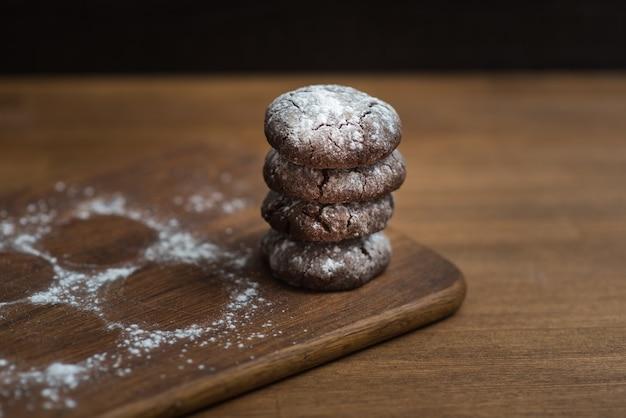 Biscuits au chocolat avec du sucre en poudre sur planche de cuisine en bois