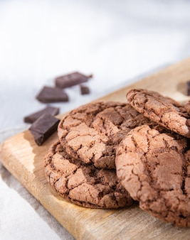 Biscuits au chocolat faits maison avec des pépites de chocolat sur une planche à découper en bois sur une table lumineuse. vue macro et gros plan