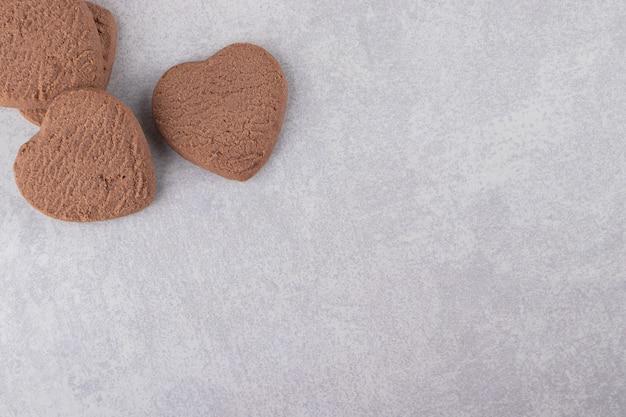 Biscuits au chocolat en forme de coeur placés sur une table en pierre.