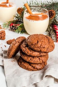 Biscuits au chocolat froissé pour noël, avec cocktail de lait de poule, canne à sucre, arbre de noël et décoration de vacances, sur blanc,