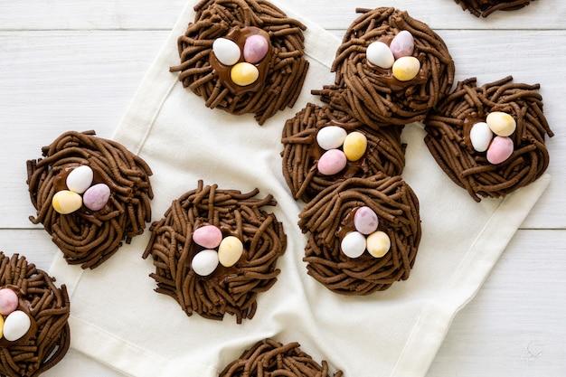Biscuits au chocolat de pâques. nids avec des œufs sucrés sur fond blanc.