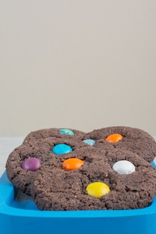 Biscuits au chocolat sucré rond sur plaque bleue.