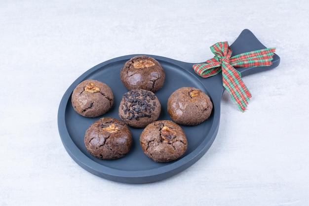 Biscuits au chocolat sur tableau noir avec ruban. photo de haute qualité
