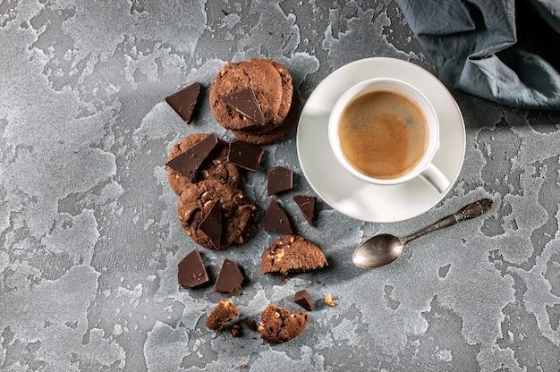 Biscuits au chocolat et une tasse de café sur un fond de béton gris. vue de dessus