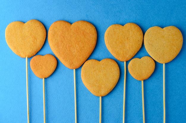Biscuits au gingembre sur un bâton en forme de coeurs sur fond bleu