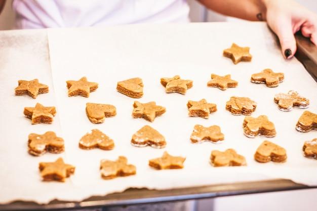 Biscuits au gingembre crus sur une plaque à pâtisserie dans les mains de la femme