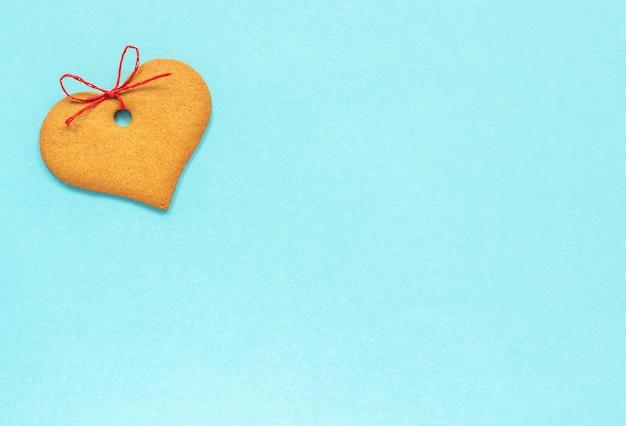 Biscuits au gingembre en forme de coeur ornés d'un arc sur fond bleu. vue de dessus copie espace carte valentine