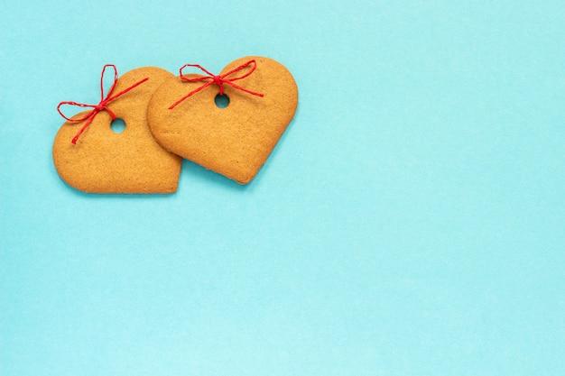 Biscuits au gingembre en forme de coeur ornés d'un arc sur fond bleu