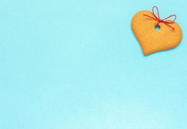 Biscuits au gingembre en forme de coeur ornés d'un arc sur fond bleu.