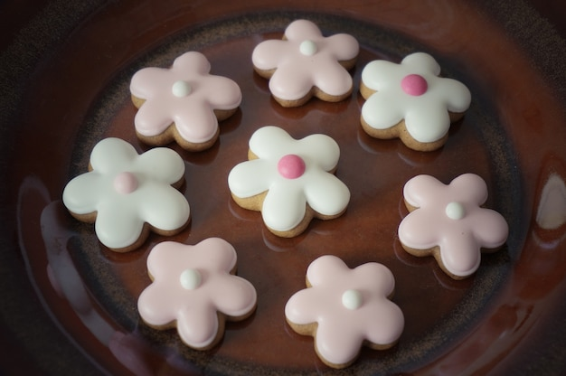 Biscuits au gingembre en forme de fleur sur une plaque en céramique brune