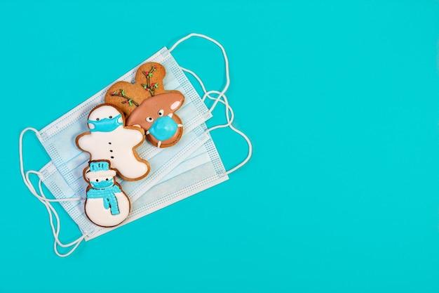 Biscuits au gingembre de noël drôles dans des masques de protection et un masque médical.