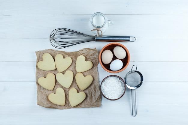 Biscuits au lait, sucre en poudre, œufs, passoire, fouet vue de dessus sur un fond en bois