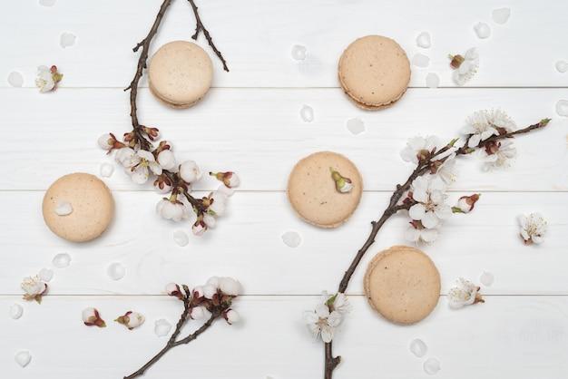 Biscuits au macaron et fleurs sur fond de bois blanc