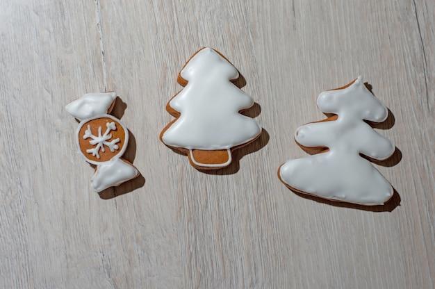Biscuits au pain d'épice festifs faits à la main sous forme d'étoiles, bonbons, bâtons, arbres de noël. sur un comptoir léger.