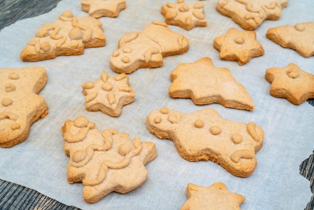 Biscuits au pain d'épices figurines de noël en pâte cuites au four. sur du papier sulfurisé.