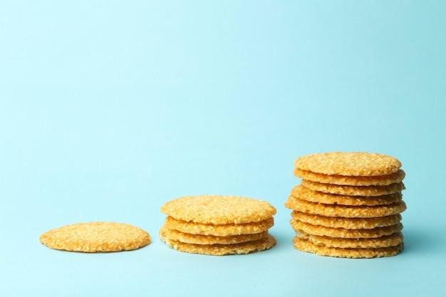 Biscuits au sésame sur fond bleu. fond de cuisson et de bonbons. concept d'infographie alimentaire