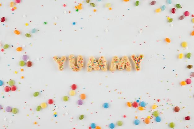Biscuits au sucre en forme de lettre faisant un mot délicieux sur table décorée de bonbons colorés