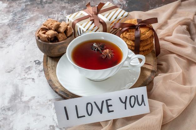 Biscuits au sucre vue de face avec une tasse de thé sur fond clair tarte couleur biscuit au thé gâteau sucré pâtisserie au sucre amour