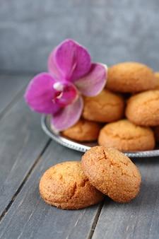 Biscuits aux amandes avec fleur d'orchidée sur une table en bois rustique