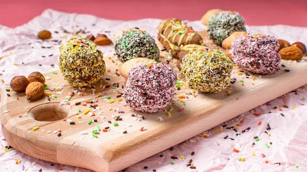 Biscuits aux amandes et à la noix de coco avec du chocolat et de la crème sur une planche de bois