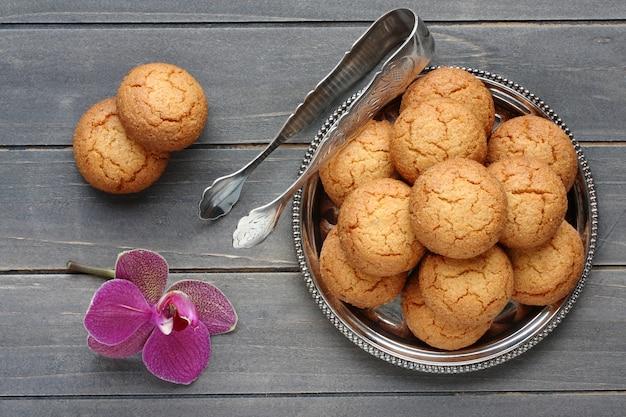 Biscuits aux amandes avec pince à sucre et fleur d'orchidée sur une table en bois rustique