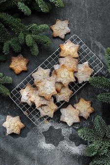 Biscuits aux amandes et sucre glace avec des branches d'arbres de noël sur un béton foncé
