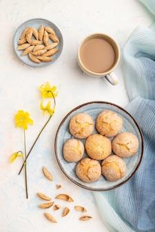 Biscuits aux amandes et une tasse de café sur un fond de béton blanc et textile en lin bleu. vue de dessus, mise à plat, gros plan.