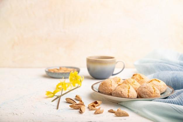 Biscuits aux amandes et une tasse de café sur un fond de béton blanc et textile en lin bleu.