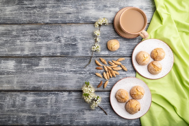 Biscuits aux amandes et une tasse de café sur un fond en bois gris et textile en lin vert. vue de dessus, mise à plat, espace de copie.