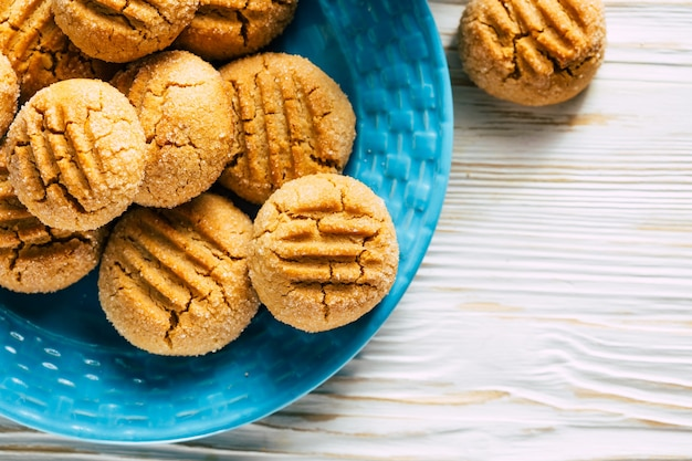 Biscuits aux arachides en plaque bleue sur fond de bois blanc