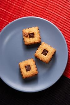 Biscuits aux brisures de chocolat empilés sur une assiette, prêts à être servis sur une assiette bleue
