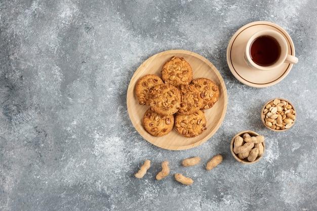 Biscuits aux cacahuètes biologiques et miel sur planche de bois avec tasse de thé.