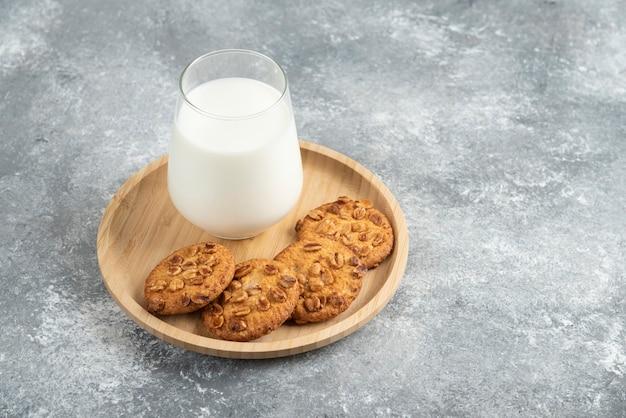 Biscuits aux cacahuètes biologiques et verre de lait sur plaque de bois.