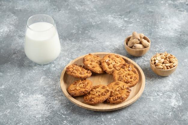 Biscuits aux cacahuètes biologiques et verre de lait sur table en marbre.