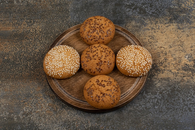 Biscuits aux graines de sésame et morceaux de chocolat sur planche de bois.