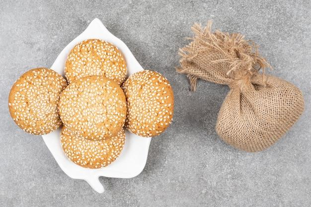 Biscuits aux graines de sésame sur plaque blanche avec un sac