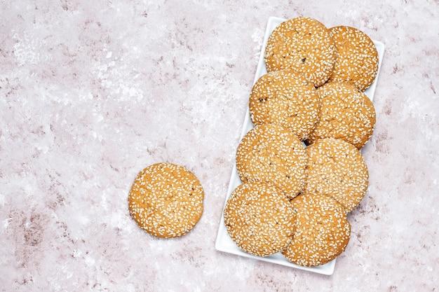 Biscuits aux graines de sésame de style américain sur fond de béton clair.