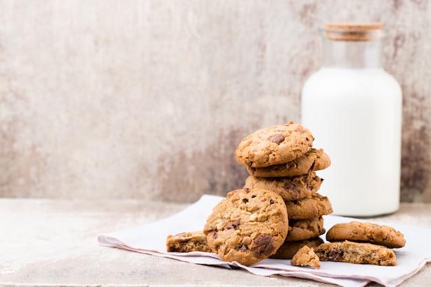 Biscuits aux pépites d'avoine au chocolat avec du lait sur la table en bois rustique.