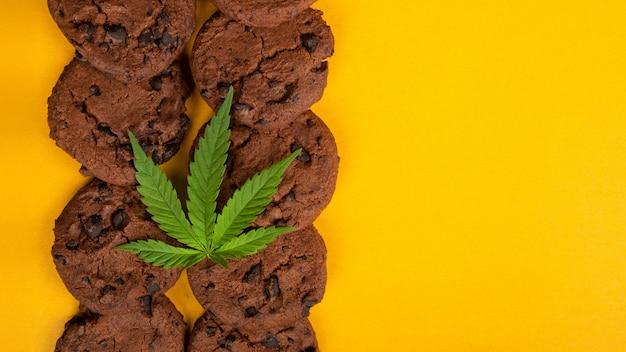 Biscuits aux pépites de chocolat au beurre de cannabis, pâtisseries sucrées au beurre de cbd sur fond jaune, espace de copie.