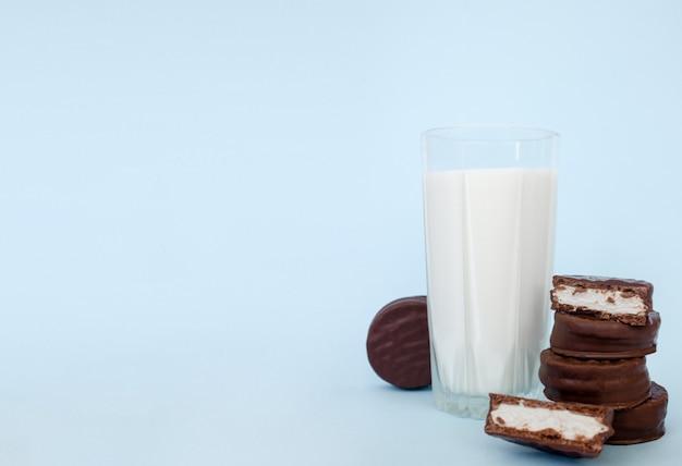 Biscuits aux pépites de chocolat avec du lait sur un espace de copie de fond bleu