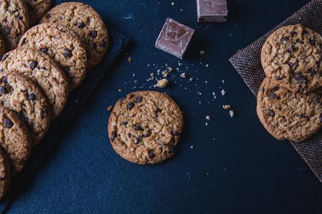Biscuits aux pépites de chocolat faits à la main et des morceaux de cacao sur une table de tableau noir. vue de dessus