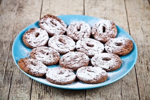Biscuits aux pépites de chocolat frais cuits au four avec du sucre en poudre sur la plaque d'immatriculation bleue sur une table en bois rustique