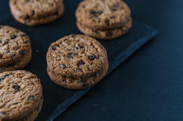 Biscuits aux pépites de chocolat à la main sur une table de tableau.