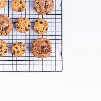 Biscuits aux pépites de chocolat maison fraîchement cuits sur un filet de four sur un fond blanc
