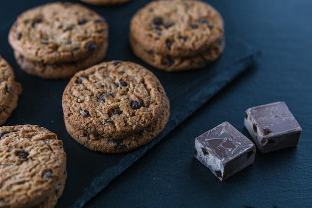 Biscuits aux pépites de chocolat et morceaux de cacao faits à la main sur un tableau noir.