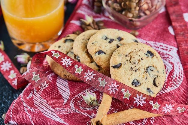 Biscuits aux pépites de chocolat sur nappe rouge avec un verre de jus et de cannelle
